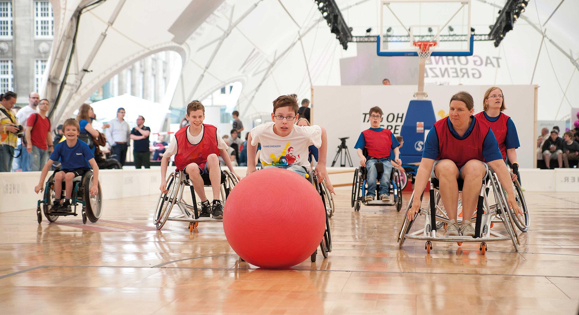 Jugendliche im Rollstuhl spielen mit einem großen Pezziball Wheel Soccer.